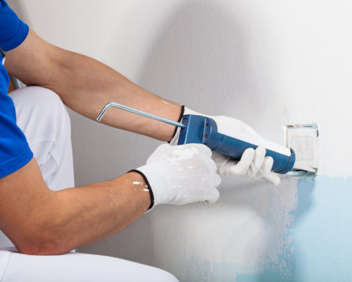 Close-up Of Professional Workman Applying Silicone Sealant With Caulking Gun on the Wall